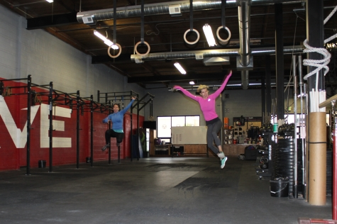 Ali and Sarah jumping for joy over dumbbells and burpees.