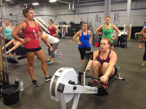 Sarah crushing calories on the rower with her team standing by.